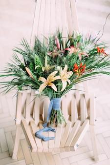 Piękny tropikalny ślubny bukiet na krześle