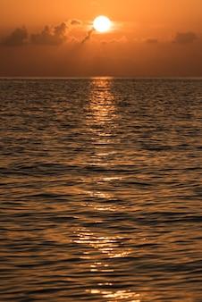 Piękny tropikalny zachód słońca na powierzchni oceanu