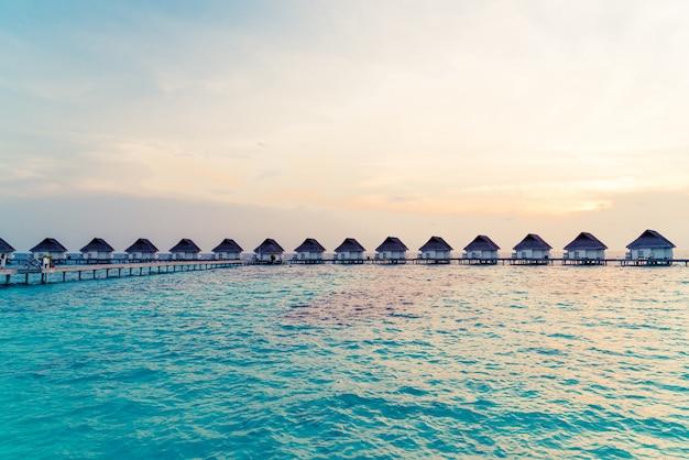 Piękny tropikalny zmierzch nad malediwy wyspą z wodnym bungalowem w hotelowym kurorcie