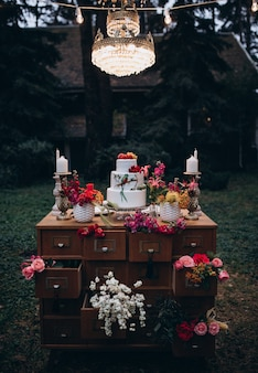 Piękny trzypoziomowy tort weselny ozdobiony ptakiem, różowymi kwiatami i gałęziami z zielonymi liśćmi w rustykalnym stylu. świąteczny deser. koncepcja ślubu.
