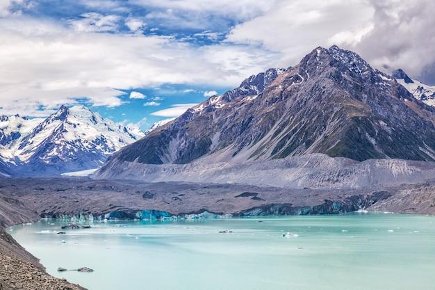 Piękny turkusowy tasman glacier lake i góry skaliste w chmurach, park narodowy mount cook, wyspa południowa, nowa zelandia