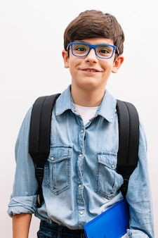 Piękny uczeń chłopiec dziecko noszenie plecaka trzymając książki na białym tle z szczęśliwą twarzą stojącą i uśmiechniętą z pewnym uśmiechem pokazując zęby