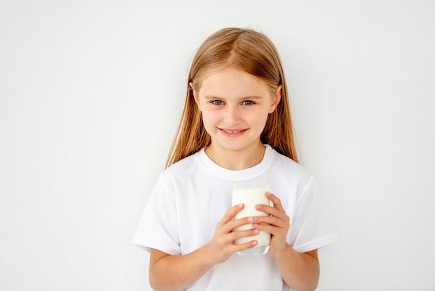 Piękny uczennica dzieciak pije ciepłego mleko