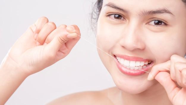 Piękny uśmiech młoda kobieta używa nici dentystycznej