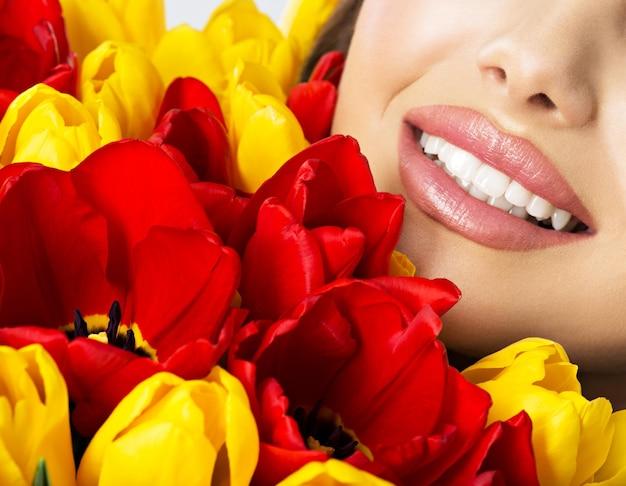 Piękny uśmiech zdrowych zębów młodej damy. pół twarzy całkiem szczęśliwej kobiety z tulipanami