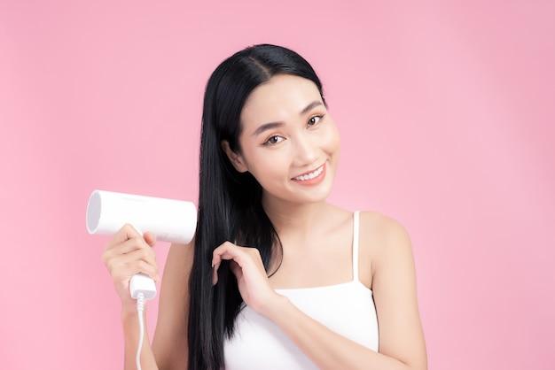 Piękny uśmiechający się azjatyckie dziewczyny z czarne długie proste włosy za pomocą suszarki do włosów. pojedynczo na różowo