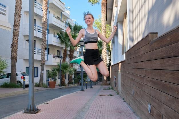 Piękny uśmiechający się wesoły sport dziewczyna nastolatek skoki, pływające w powietrzu, tło ulicy małego miasteczka. aktywny, wysportowany, zdrowy styl życia, młodzież młodzieżowa