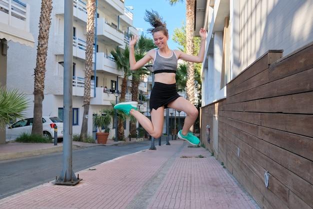 Piękny uśmiechający się wesoły sport dziewczyna nastolatek skoki, pływające w powietrzu, tło ulicy małego miasteczka. aktywny, wysportowany, zdrowy styl życia, młodzieżowa młodzież