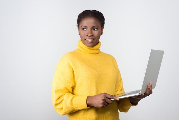 Piękny uśmiechnięty amerykanin afrykańskiego pochodzenia kobiety mienia laptop