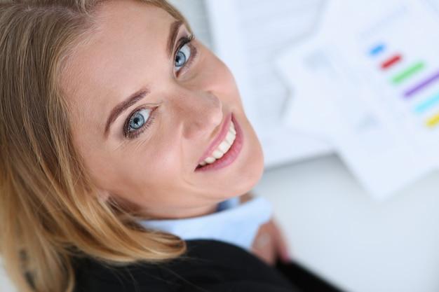 Piękny uśmiechnięty bizneswomanu portret przy miejscem pracy