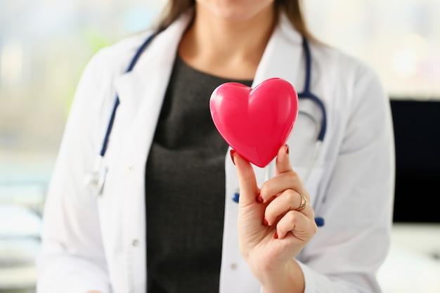 Piękny uśmiechnięty blond kobiety lekarki chwyt w ręki czerwieni zabawki serca zbliżeniu. kardio terapeuta edukacja studentów cpr 911 ratuj życie lekarzowi wykonuj pomiar arytmii tętna