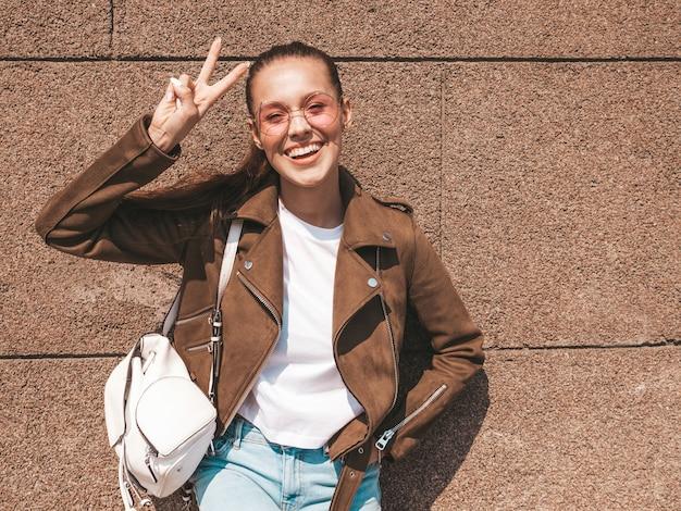 Piękny uśmiechnięty brunetka model ubierał w lato modnisia kurtce i cajgach odziewa pokazywać znaka pokoju