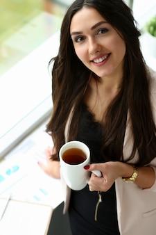 Piękny uśmiechnięty dziewczyna chwyt w ręki filiżance