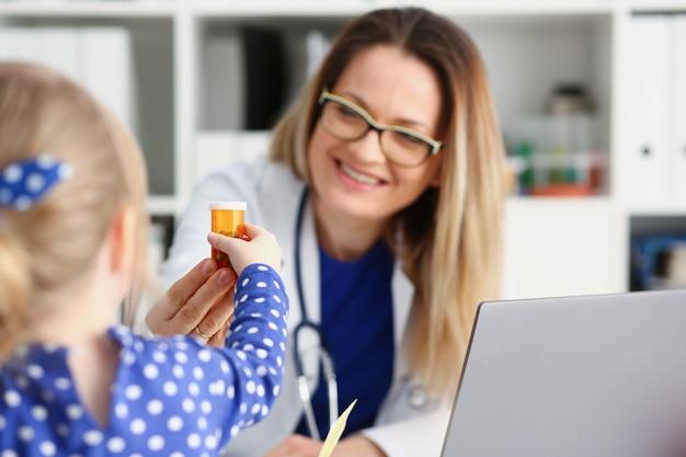 Piękny uśmiechnięty kobiety lekarki chwyt w ręki pigułce
