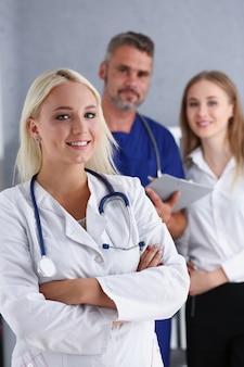 Piękny uśmiechnięty kobiety lekarki stojak w biurze