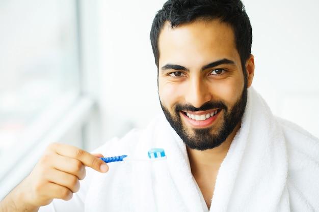 Piękny uśmiechnięty mężczyzna szczotkuje zdrowe białe zęby szczotką. obraz w wysokiej rozdzielczości