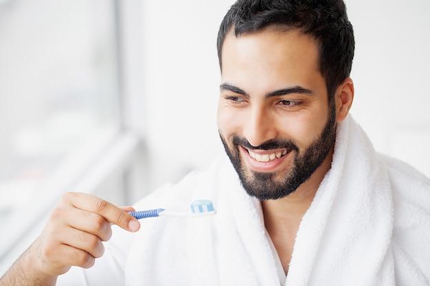 Piękny uśmiechnięty mężczyzna szczotkuje zdrowe białe zęby szczotką