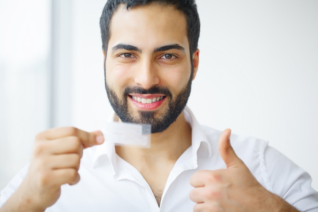 Piękny uśmiechnięty mężczyzna trzyma pasek wybielający