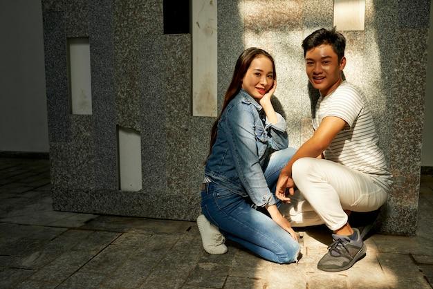 Piękny uśmiechnięty młody chłopak i dziewczyna pozują pod ścianą na podziemnym parkingu