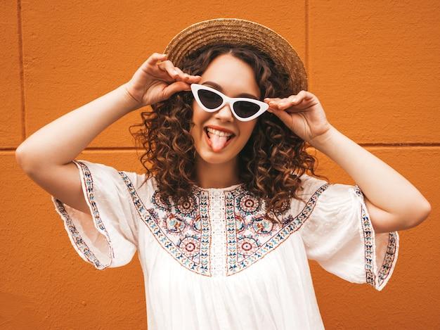 Piękny uśmiechnięty model z fryzurą afro loki ubrany w letnią białą sukienkę hipster i okulary przeciwsłoneczne