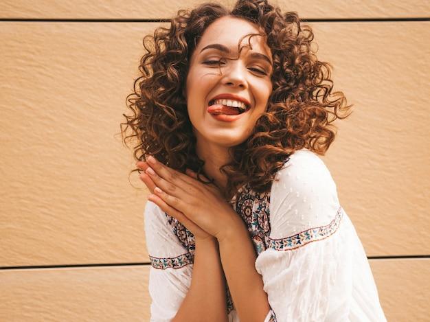 Piękny uśmiechnięty model z fryzurą afro loki, ubrany w letnią białą sukienkę hipster.