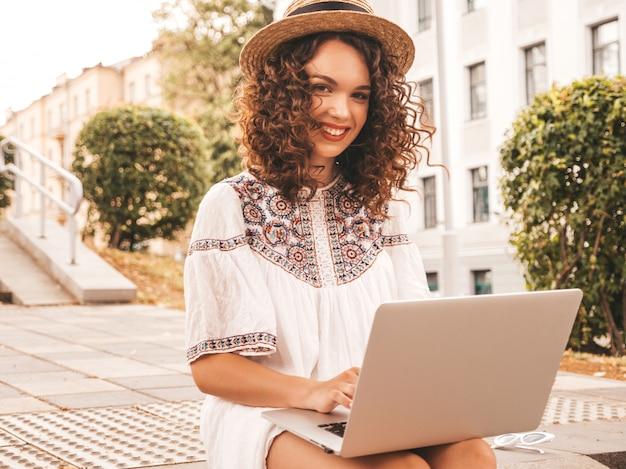 Piękny uśmiechnięty model z fryzurą afro loki w letniej hipster białej sukni i kapeluszu.