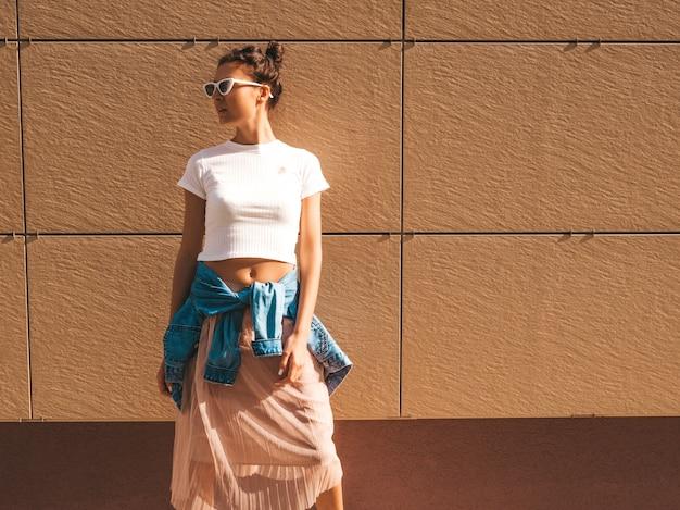 Piękny uśmiechnięty model z rogami fryzura ubrana w letnie ubrania hipster biały t-shirt. seksowna beztroska dziewczyna pozuje na ulicy w pobliżu ściany. modna zabawna i pozytywna kobieta zabawy w okularach przeciwsłonecznych