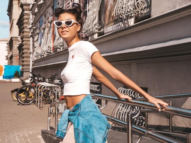 Piękny uśmiechnięty model z rogami fryzura ubrana w letnie ubrania hipster kurtka dżinsy. seksowna beztroska dziewczyna pozuje na ulicy. modna śmieszna i pozytywna kobieta ma zabawę w okularach przeciwsłonecznych