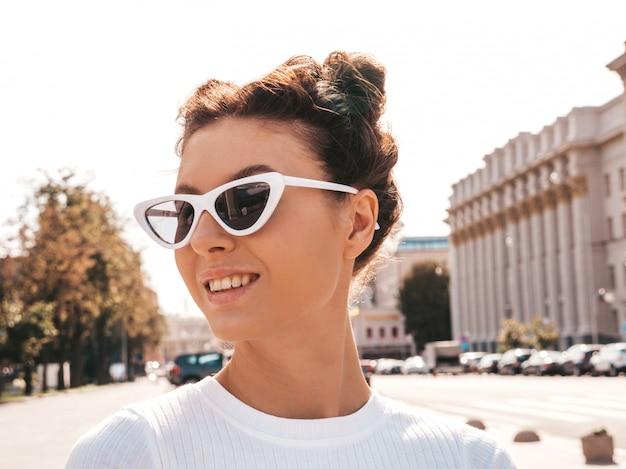 Piękny uśmiechnięty model z rogami fryzura ubrana w letnie ubrania hipster. seksowna beztroska dziewczyna pozuje na ulicy. modna śmieszna i pozytywna kobieta ma zabawę w okularach przeciwsłonecznych