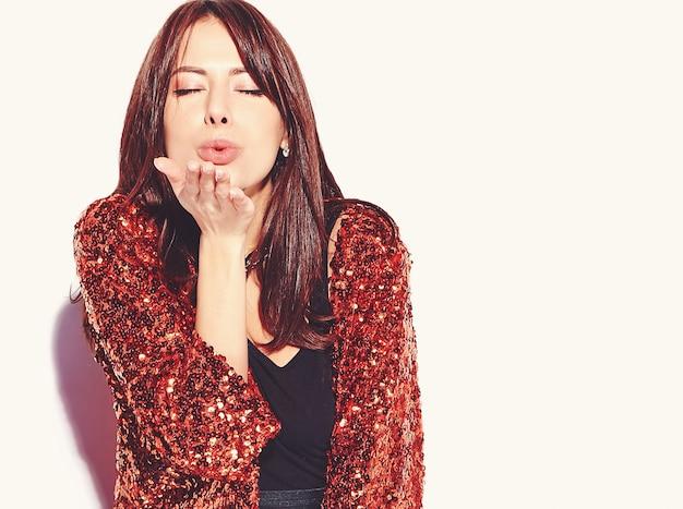 Piękny uśmiechnięty modniś brunetki kobiety model w jaskrawych nowożytnych eleganckich lat ubraniach odizolowywających. pocałunek