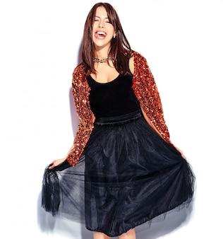 Piękny uśmiechnięty modniś brunetki kobiety model w jaskrawych nowożytnych eleganckich lat ubraniach odizolowywających. pokazać język