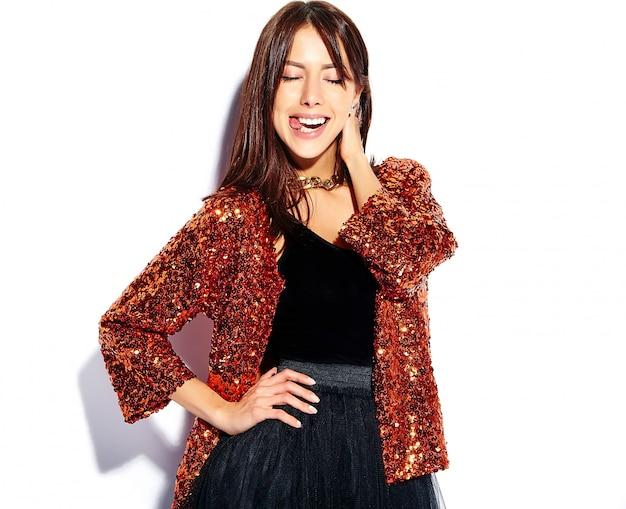 Piękny uśmiechnięty modniś brunetki kobiety model w jaskrawych nowożytnych eleganckich lat ubraniach odizolowywających. pokazując jej język