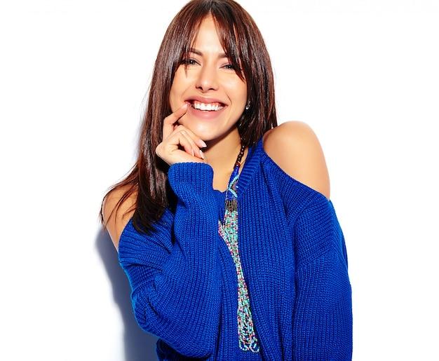 Piękny uśmiechnięty modniś brunetki kobiety model w przypadkowego eleganckiego lata błękitnym pulowerze odizolowywającym na białym tle