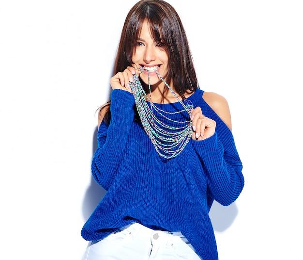 Piękny uśmiechnięty modniś brunetki kobiety model w przypadkowego stylowego lata błękitnym pulowerze odizolowywającym na białym tle, gryźć jej akcesoria