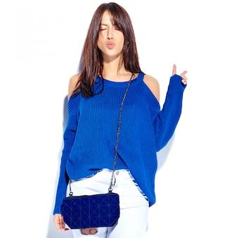 Piękny uśmiechnięty modniś brunetki kobiety model w przypadkowym eleganckim lato pulowerze i błękitnej torebce odizolowywających na białym tle pokazuje pokoju znaka i daje buziakowi