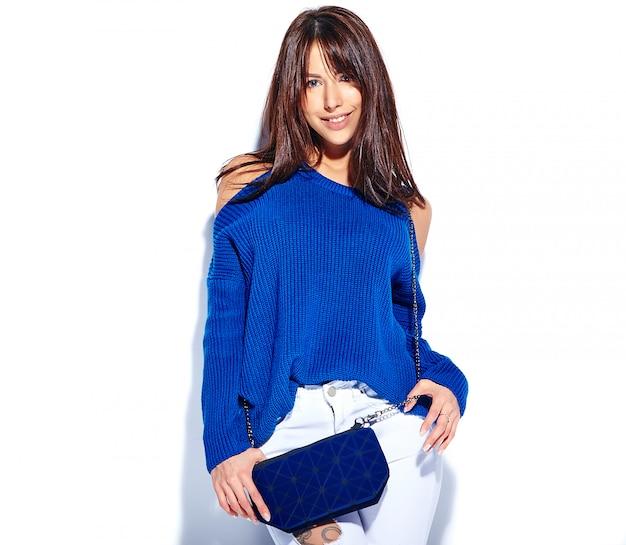 Piękny uśmiechnięty modniś brunetki kobiety model w przypadkowym eleganckim lato pulowerze i błękitnej torebce odizolowywających na białym tle