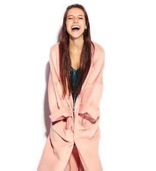 Piękny uśmiechnięty modniś brunetki kobiety model w stylowym różowym płaszczu