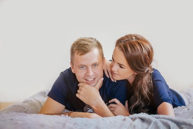 Piękny uśmiechnięty pary przytulenie i lying on the beach na łóżku w domu