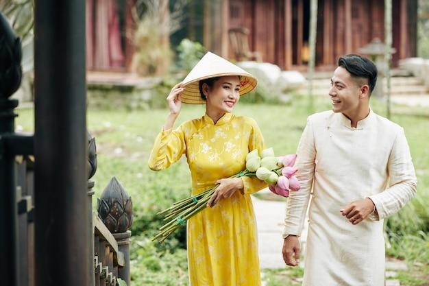 Piękny uśmiechnięty wietnamski mężczyzna i kobieta w sukienkach ao dai trzymających kwiaty lotosu podczas wchodzenia do starego budynku