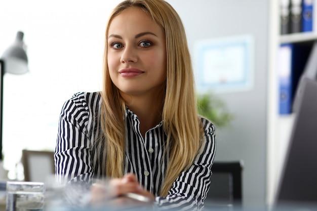 Piękny uśmiechnięty żeński ceo przy stołu roboczego patrzeć