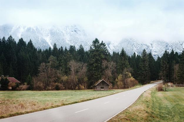 Piękny uspokajający droga krajobraz na tle śnieżne góry, włochy, dolomity. krajobrazy górskiej drogi późną jesienią w spokojnych, ciepłych kolorach. podróż samochodem