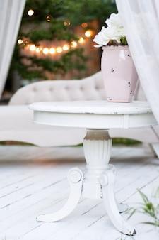 Piękny wazon ogrodowy z białymi różami i innymi kwiatami na stole, na zewnątrz, pomysł na altanę.