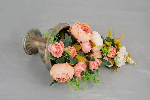 Piękny wazon z różowymi różami na szarym stole.