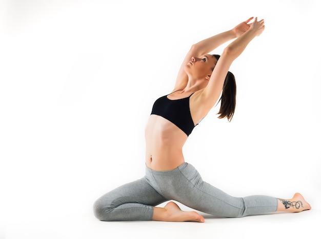 Piękny wdzięczny młody sportowiec kaukaski kobieta robi ćwiczenia żaby, leżąc na dywanie na podłodze na białej ścianie. koncepcja elastycznego pleców i stawów.