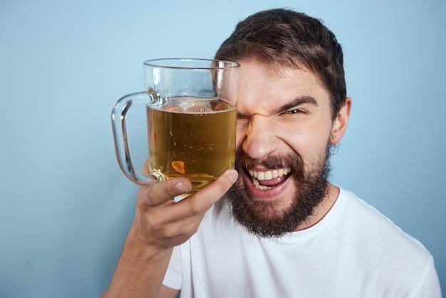Piękny wesoły mężczyzna w białej koszulce z kuflem piwa pijany na niebiesko
