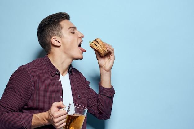 Piękny wesoły pijany mężczyzna z kuflem piwa i hamburgerem w ręku