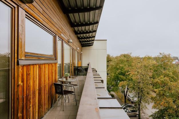 Piękny widok na długi pusty balkon hotelowy z małymi stolikami?