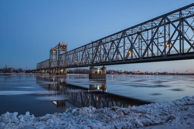 Piękny widok na dryf lodu pod mostem kolejowym w archangielsku w rosji. piękny ruch lodu na północnej dźwinie, wieczorny krajobraz.