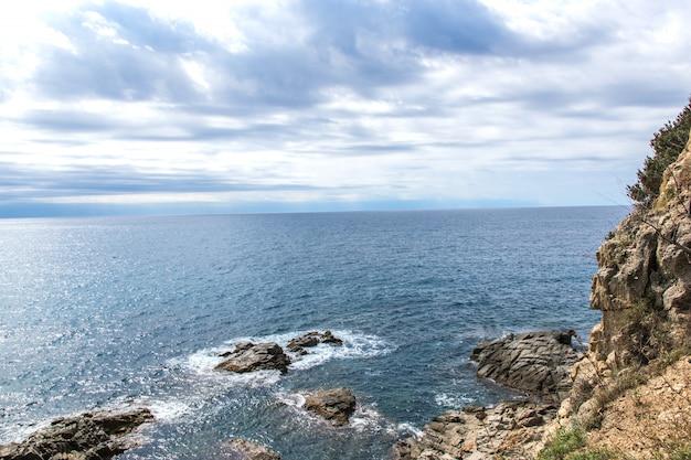 Piękny widok na fale morskie, skały, kamienie i chmury na niebie.