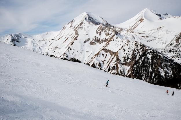 Piękny widok na góry zimą i bawiących się kilku narciarzy.